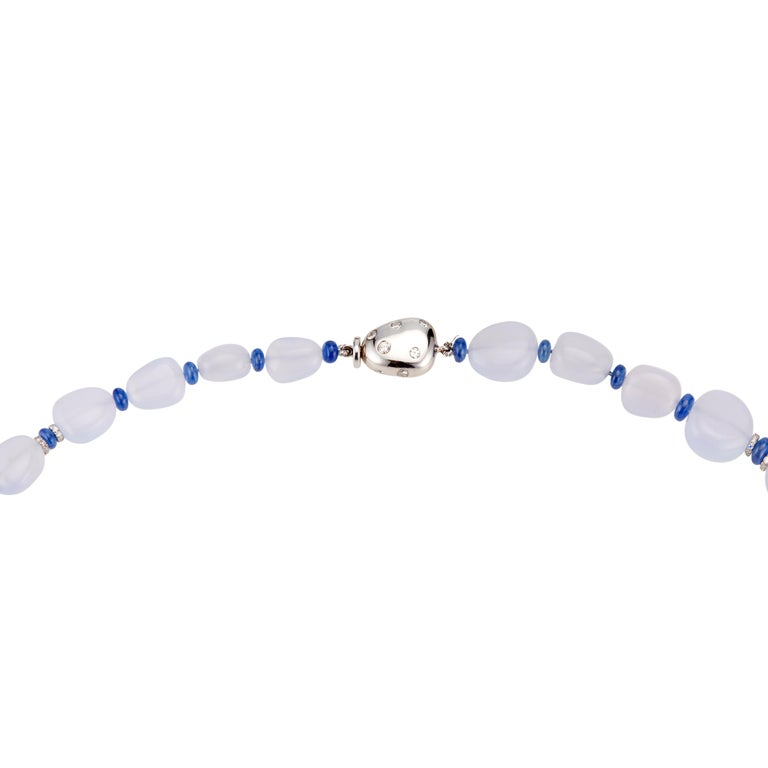 Translucent blue natural chalcedony beads with with genuine sapphire separators and 18k white gold rondells with round brilliant cut diamonds. 18k white gold diamond catch. 26 inches   43 pale blue chalcedony beads 44 blue sapphire rondell beads
