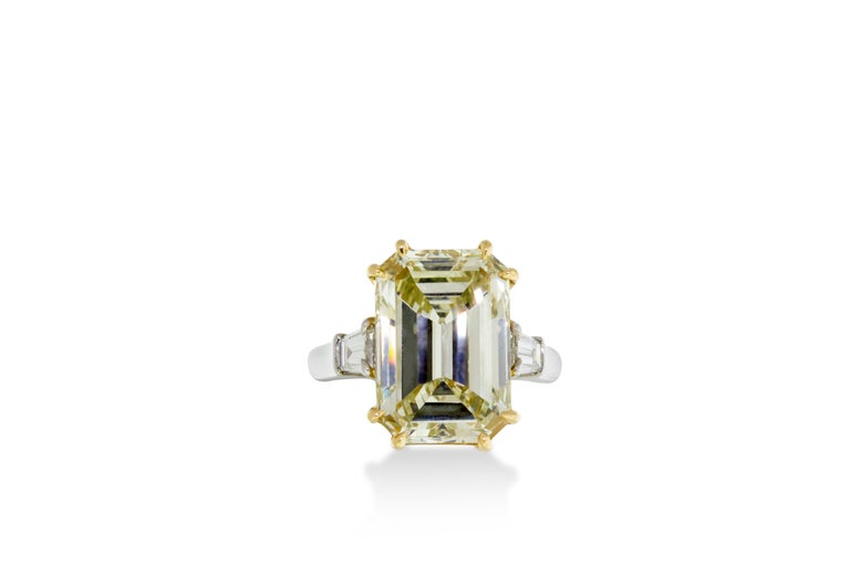A 7.52 VVS2 fancy light yellow emerald cut diamond flanked on either side by a tapered baguette cut diamond. Mounted in 18K yellow gold and platinum. GIA certified. Report No. 2165553057. Size 6.    Resizing available upon request.   Viewings