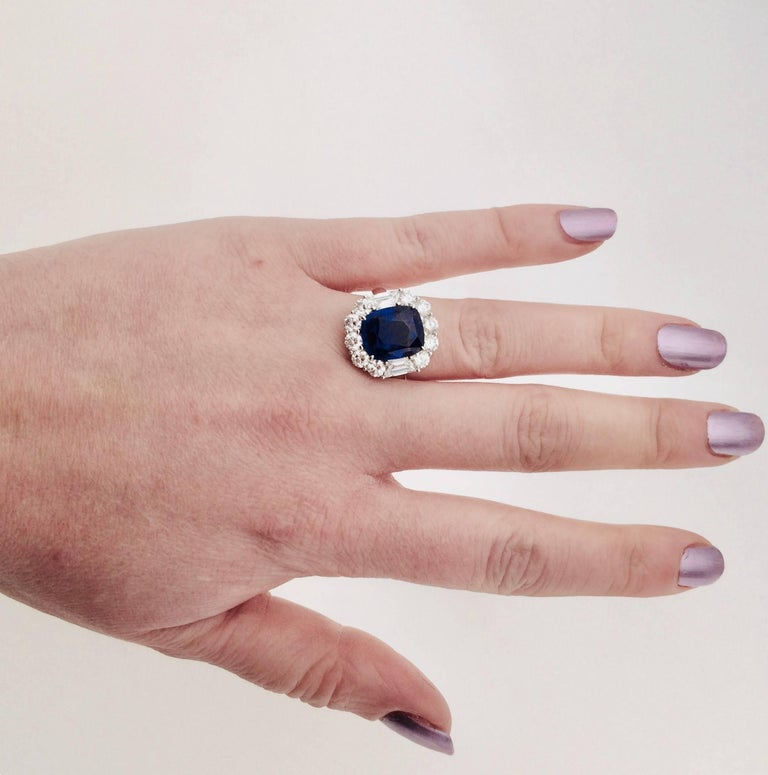 A gorgeous sapphire and diamond cluster engagement ring in platinum. The ring is formed of a cushion shaped faceted 7.62 carat sapphire set in a four claw setting. The sapphire is embellished by 2.15 carats of diamonds forming the outer detail, with