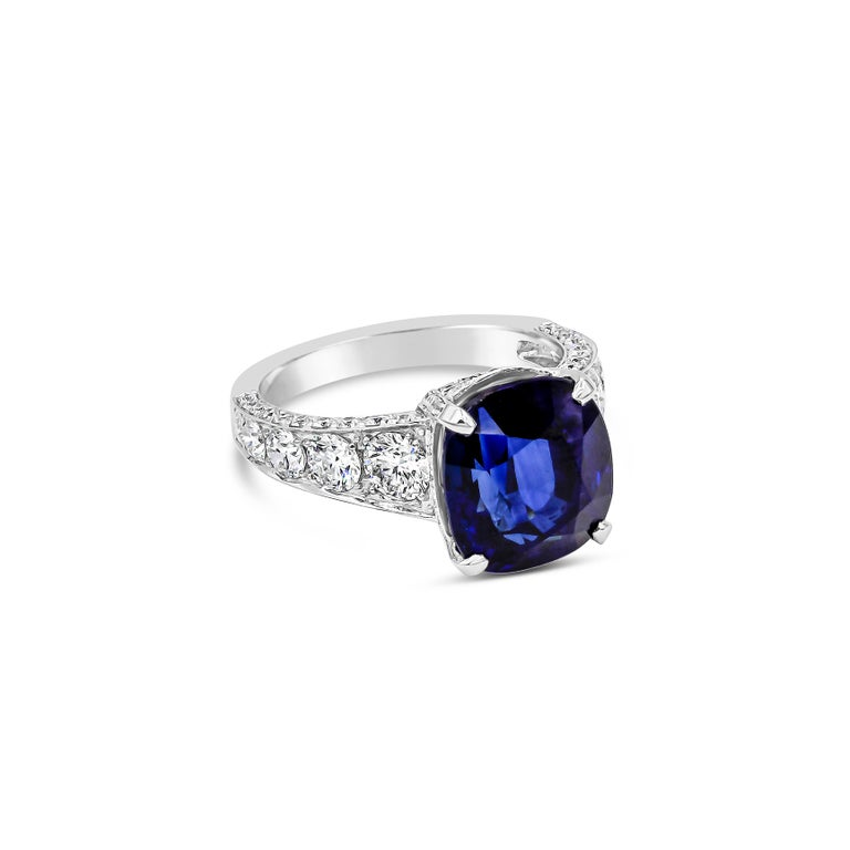 Features a color-rich royal blue sapphire weighing 7.66 carats, set in a diamond encrusted basket. Flanking either side of the sapphire are round brilliant diamonds that graduates smaller as it gets farther from the center. 18 karat white gold