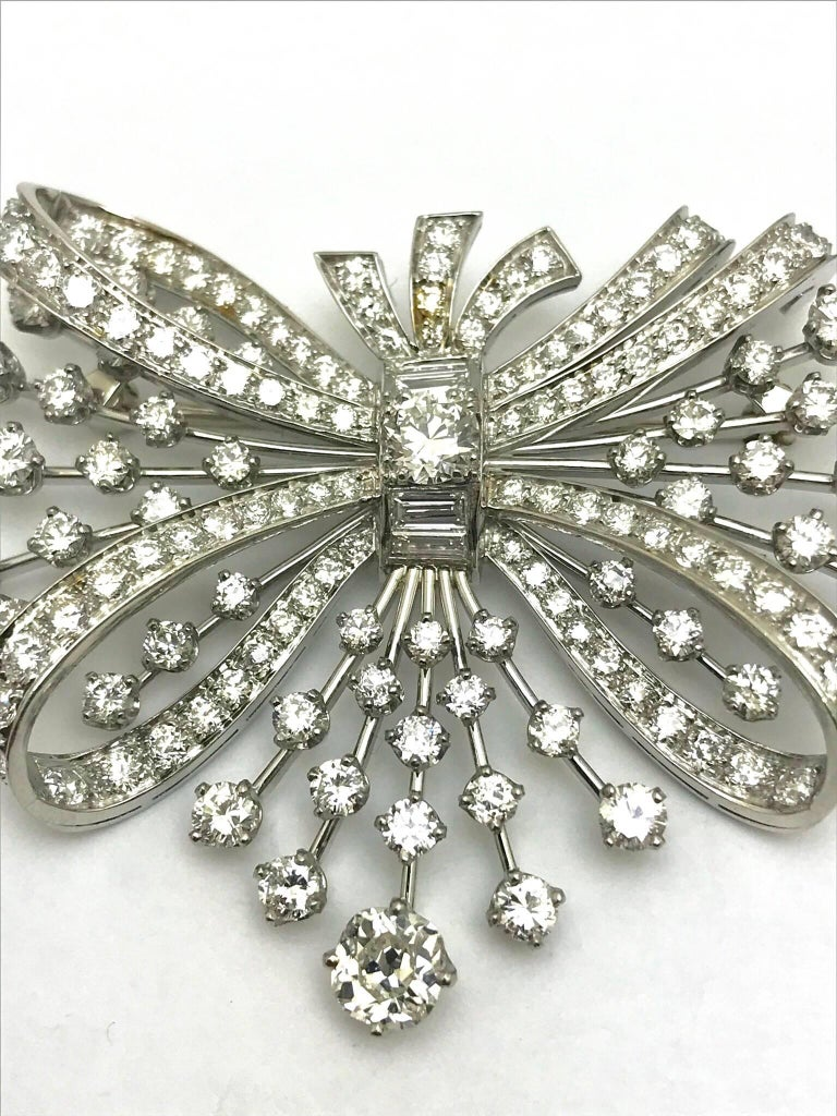 A 7.67 carats round and baguette diamond platinum spray bow brooch.  The bow has diamonds set throughout, and the spray has diamond spaced out on stems of platinum.  There are 151 round diamonds and four baguette diamonds, graded as G-I color, VS