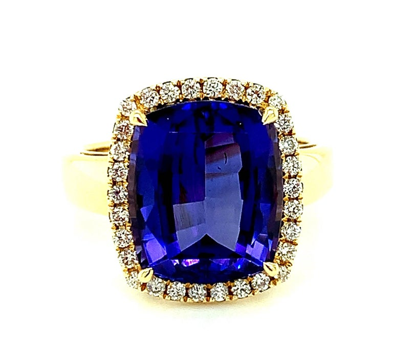 This stunning, quintessential cocktail ring features a spectacular gem-quality tanzanite with intense, violet blue color. The tanzanite is cushion shaped and weighs an impressive 7.70 carats! It is surrounded by a halo of sparkling, brilliant cut
