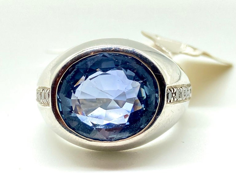 A beautiful white gold ring with an oval cut light blue Ceylon sapphire measuring 7.80 carats, bordered by 0.15 carats of round brilliant cut diamonds. Circa 1970. Certificate available.