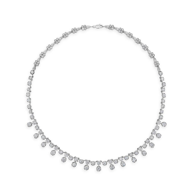 A modern and chic necklace style showcasing round brilliant diamonds weighing 7.81 carats total; Set in a starburst-like setting made in 18 karat white gold. A very brilliant piece of jewelry. 16 inches in length.