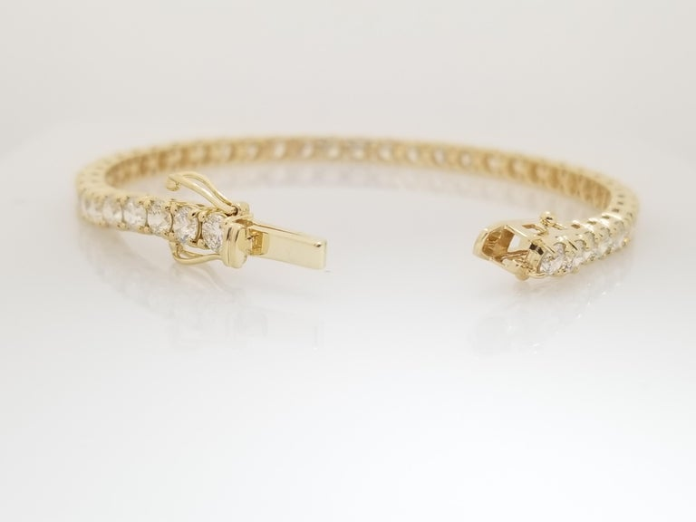 A quality tennis bracelet, round-brilliant cut diamonds. set on 14k yellow gold. each stone is set in a classic four-prong style for maximum light brilliance.   7 inch length.   Average Color H Average Clarity VS 3.9 mm wide.