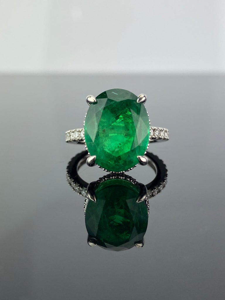 A gorgeous engagement ring, with a 7.87 carat transparent natural Zambian Emerald centre stone with Diamonds. The emerald is of great lustre and has an ideal colour. All set in solid 18K white gold. Currently a ring size US 6, but we can resize the