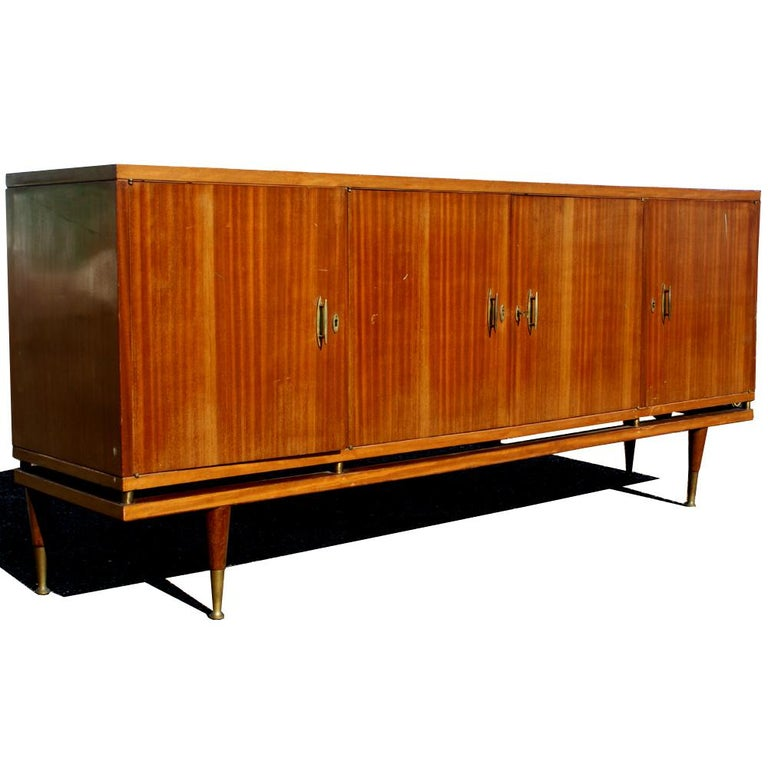 A mid century modern buffet or credenza of Italian design.  Four doors concealing shelved storage and two drawers. Age apprpriate wear.
