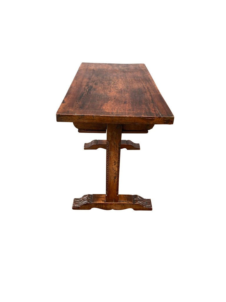 Small table with rectangular top over two carved drawers, square trestle supports, stretcher and flat carved feet.