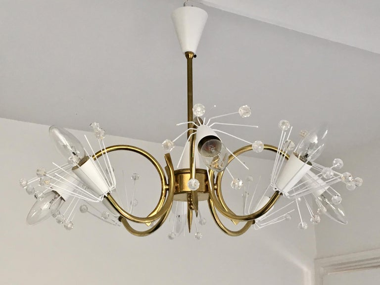 A mid-20th century 8-arm chandelier, attributed to Emil Stejnar for Rupert Nikoll of Austria. A charming and delicate piece, with white decorated cones, a brass frame and original ceiling canopy.  The frame is in good condition, with aged patina
