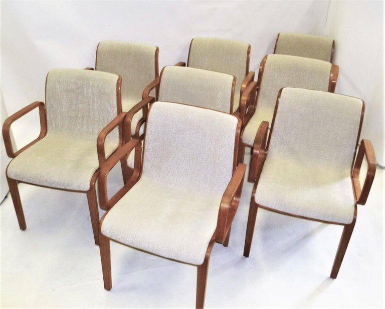 Designed in the mid-1960s by Bill Stephens (1932-2007) for Knoll, these eight midcentury armed dining chairs in blond oak have been newly reupholstered with a neutral soft ribbed bouclé fabric. Produced in the early 1970s, most have remnants of
