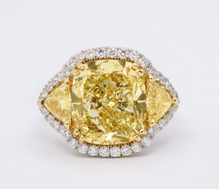 An incredible yellow diamond set in a unique custom mounting.   This diamond has a rich yellow color and is full of life.  GIA certified 8.33 carat Fancy Yellow VS1 cushion cut diamond.   Approximately 1.50 carats in matching yellow diamond