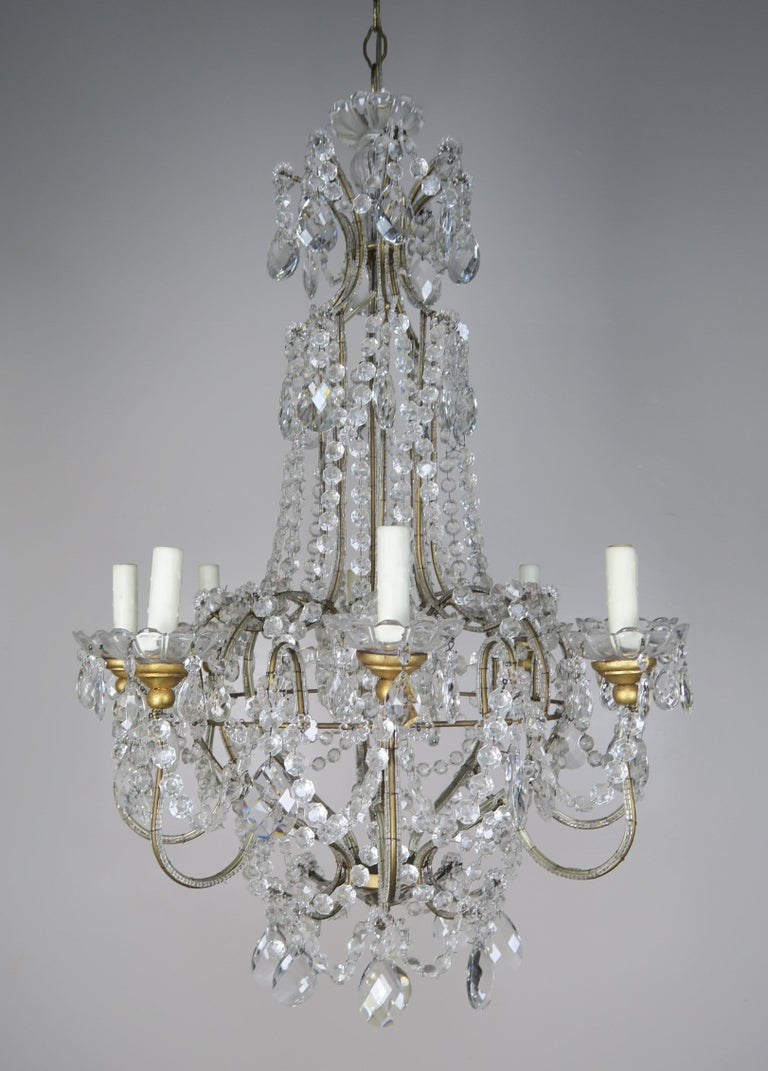 Eight-light crystal beaded arm chandelier adorned with garlands of English cut beads. The garlands of beads drape down into the body of the fixture. Almond shaped faceted crystals can be seen throughout as well. The chandelier has an antique gold