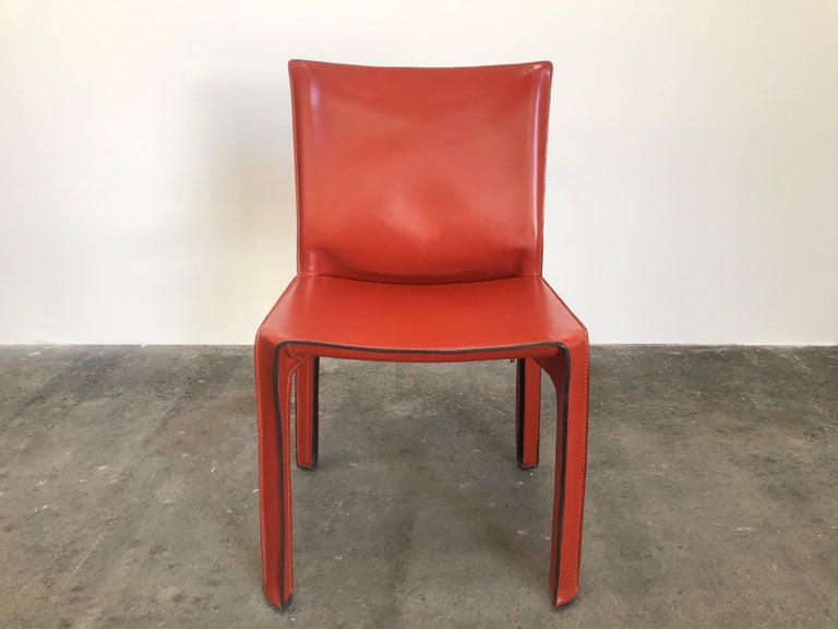 Set of 8 Mario Bellini CAB 412 chairs, made by Cassina in the 1980s. Flexible steel frame covered with a skin of high quality Russian Red (also known as Bulgarian Red) saddle leather. This elegant, versatile chair is equally suitable for the dining