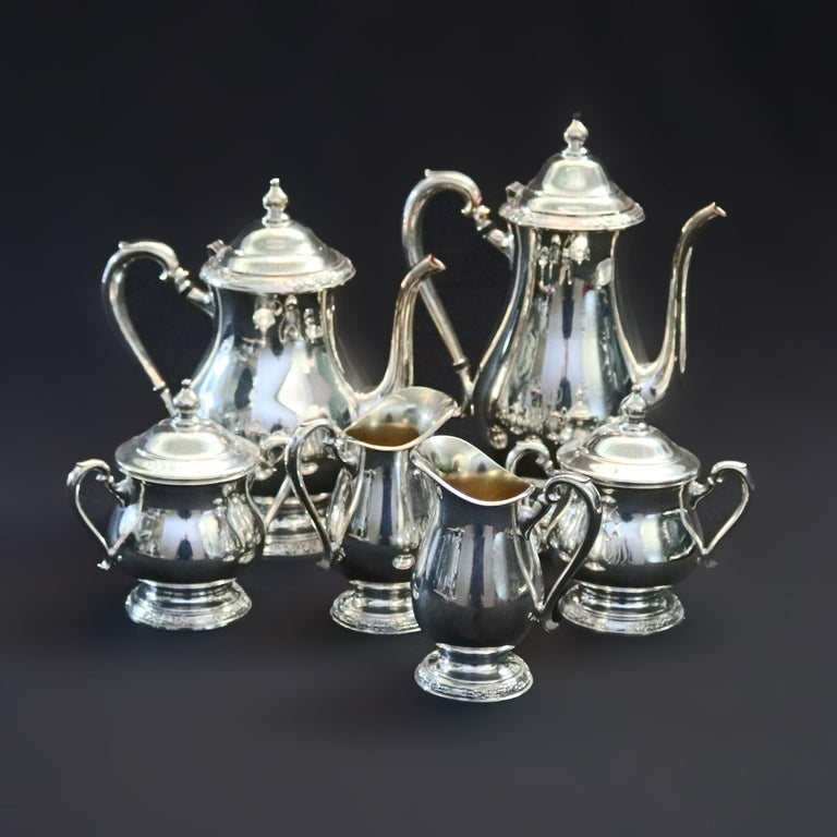 An eight-piece silver plate coffee and tea service offers bulbous form with footed bases with