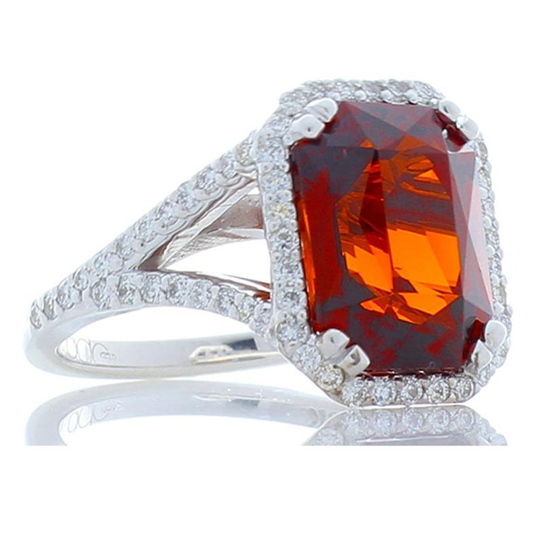 You will delighted with this vivid orangey-red 8.05 carat - 12.10 x 8.91 millimeter Spessartite garnet from Madagascar. The radiant cut is atypical for Spessartites. Its transparency, luster, and clarity are exceptional. The decadent gemstone is