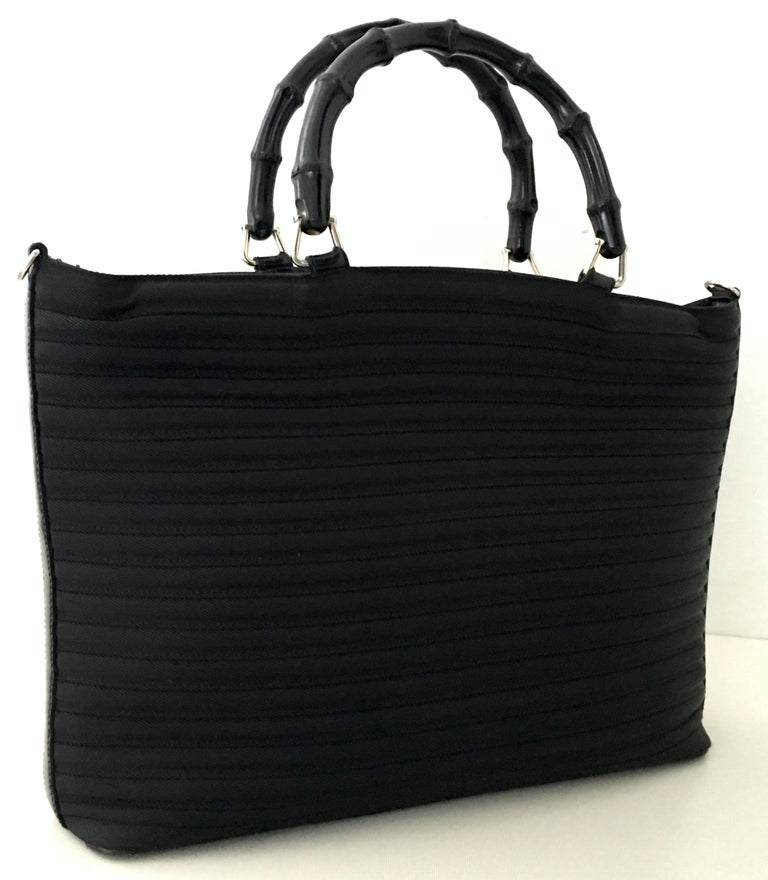 1980'S Gucci black pleated nylon, leather trim and faux bamboo wood handle two-way large tote hand bag. Includes detachable leather strap. Features silver chrome hardware, wood faux bamboo toggle zipper close,  fully lined Gucci monogram lined
