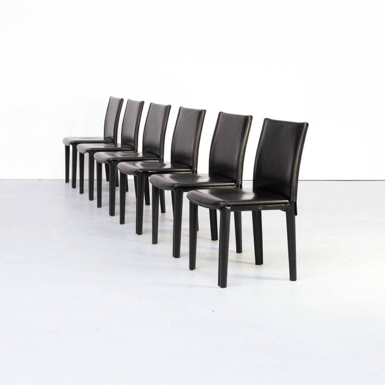 Arper mainly surprises with modernistic designs combined with a lot of comfort.These high back dining room chairs are in black leather on metal frames. Set in good condition consistent with age and use.