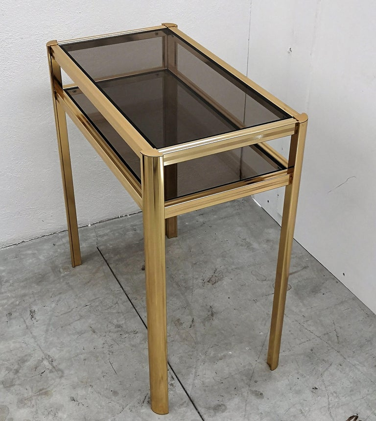 Beautiful and stylish vintage 1980s Italian brass console with two smoked glass shelves.  A great piece that perfectly adds to every home decor the typical glitz, glamour and gold of Hollywood Regency style, with a nod to Art Deco decadence and