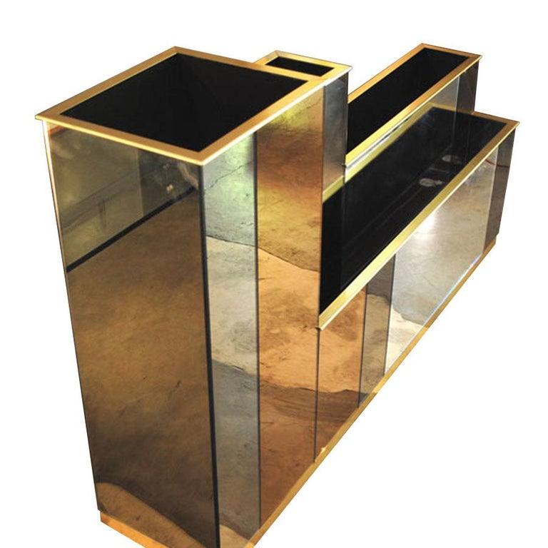 A planter front the Italian midcentury 1980s. Wooden structure completely covered with colored mirrors of different colors, gold metal finishes.
