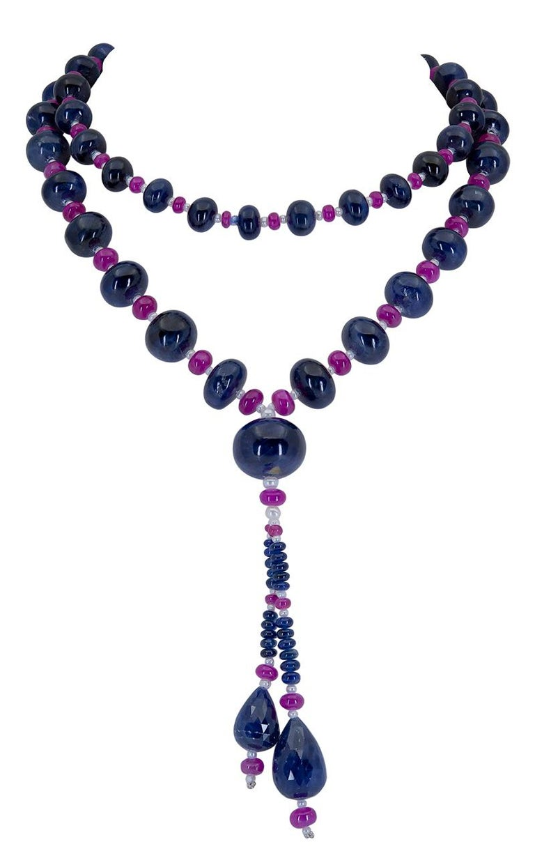 Showcasing a row of sapphire beads spaced by small rubies in-between. Dropping from the necklace are two semi-pear shape beads.  31 inch length. 4 inch drop.