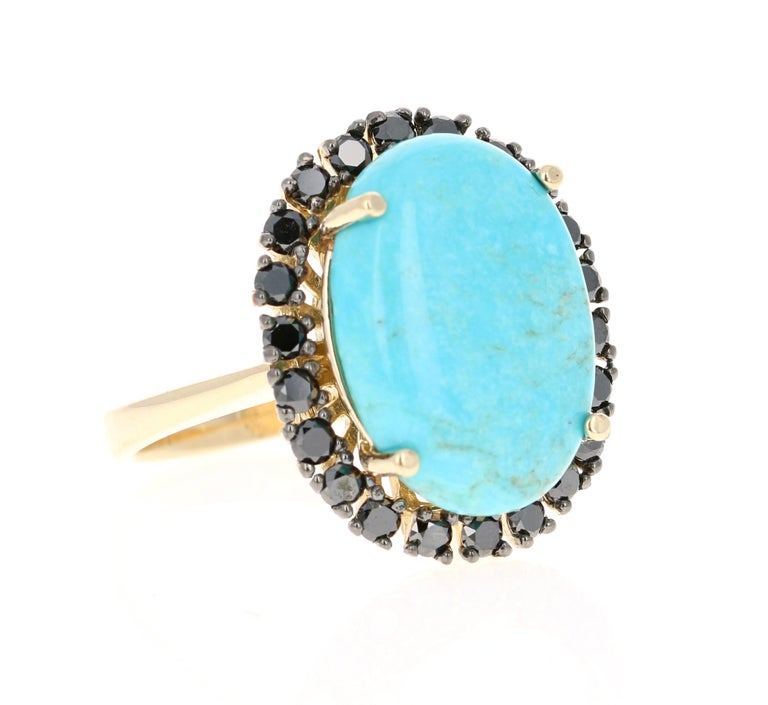 This ring has a 7.11 Carat Oval Cut Turquoise and is surrounded by 24 Black Round Cut Diamonds that weigh 1.12 Carats. The total carat weight of the ring is 8.23 Carats. The turquoise measurements are approximately 14 mm x 19 mm.  The ring is