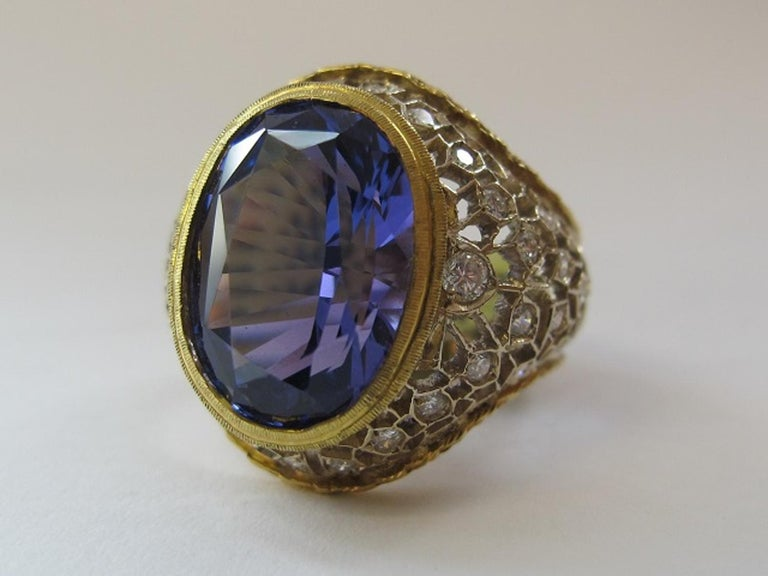 A deep, periwinkle blue tanzanite is featured in this beautiful ring set with round brilliant cut diamonds. The intricately pierced and engraved details of this ring underscore the care taken to make it. Fine craftsmanship, as showcased in this