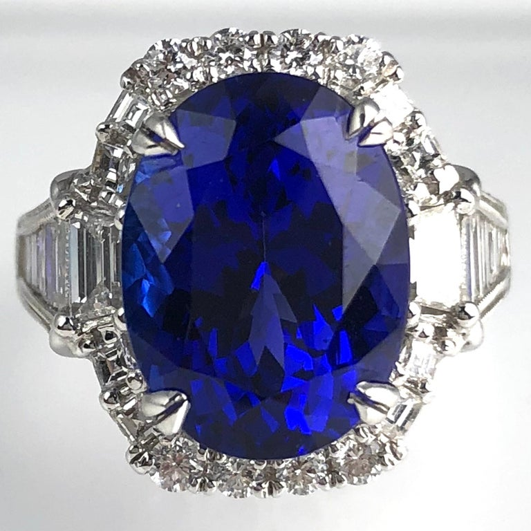 This gorgeous ring holds an 8.30 carat oval cut bluish violet Tanzanite center, surrounded by a halo of round and baguette diamonds. Additional baguette diamonds decorate the side shank.  Center: 8.30 Carat oval cut Tanzanite Total diamond weight