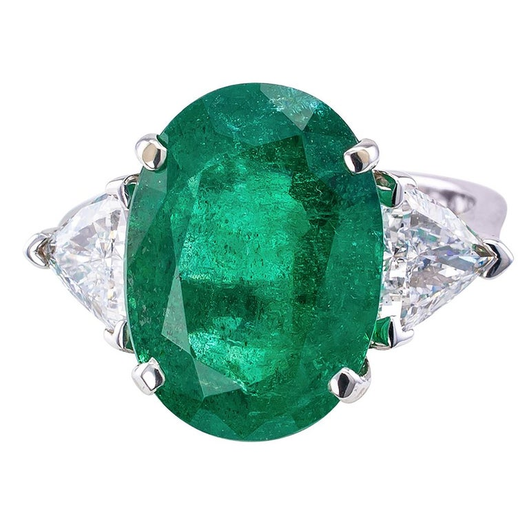 8.32 carat emerald and diamond white gold ring circa 1990. Showcasing a large oval emerald weighing 8.32 carats, between a pair of trilliant-cut diamonds totaling approximately 1.50 carats, approximately G – H color and VS clarity, mounted in
