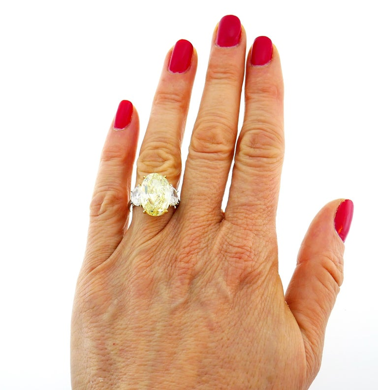 Magnificent and classy yellow diamond solitaire ring! Features a 8.47-carat natural fancy yellow oval brilliant cut diamond flanked by two half-moon cut white diamonds. The fancy yellow diamond comes with a GIA Colored Diamond Grading Report stating