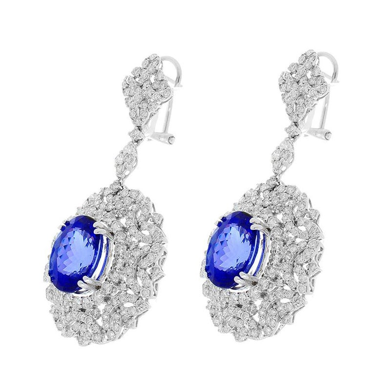 These earrings swing and glow like chandeliers in the finest hotel. Originated from the foothills of Mt. Kilimajaro in Tanzania, 8.70 carats of deep blue tanzanite are delicately prong set within a dazzling array of 6.03 carats of brilliant