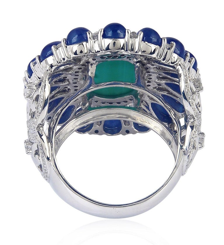This beautiful ring is handmade from 18-karat gold, 8.91 carat blue sapphire, 5.7 carat turquoise & illuminated with .99 carats diamonds.   The ring is a size 7 and may be resized to larger or smaller upon request. Please note that carat weights may