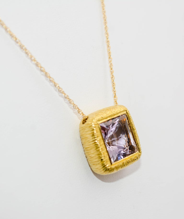 It's hip to be square if you are an 8.98 carat square brilliant cut lavender Amethyst. This exquisite Amethyst is expertly bezel set in 18 karat yellow gold with brushed grooves, and suspended on an 18 inch length chain.