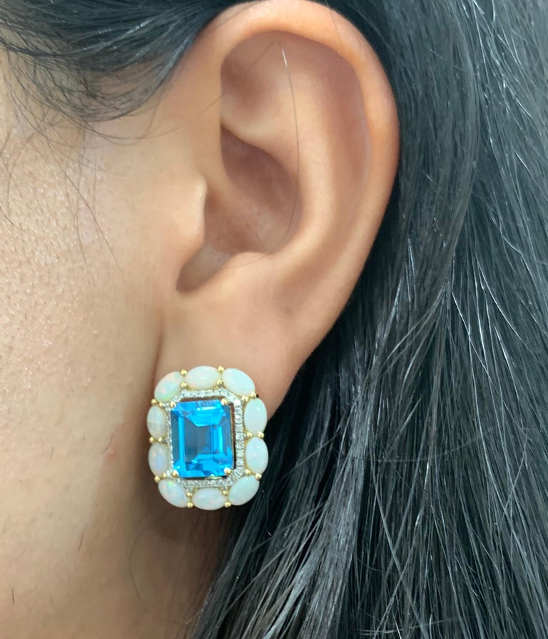 Material: 18K Yellow Gold  Stone Details: 2 Emerald Cut Blue Topaz at 8.99 Carats Total Surrounding Stone Details: 20 Oval Opals at 2.87 Carats Diamond Details: 72 Brilliant Round White Diamonds at 0.28 Carats - Clarity: SI / Color  Fine