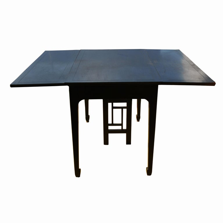 Far East collection    1960s. A dining table designed by Michael Taylor and made by Baker showing an Asian influence. Solid construction in an ebonized walnut finish. Incised apron and tapered Ming style legs. 4 leaves  Table extends to 8 ft.