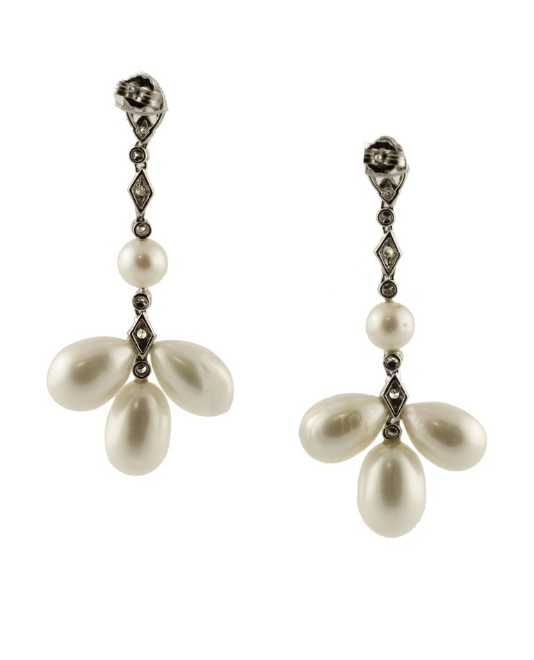 Unusual and elegant chandelier earrings mounted with 9 g of 6 white glossy drop shape pearls (13 mm X 9 mm) and 2 white glossy round shape pearls (7mm) adorned with an amazing structure in 14K white gold studded by 0.45 ct of white