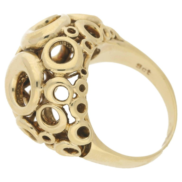 A pierced circular design openwork 9k yellow gold dress ring with stylized overlapping ringlets. Hallmarked for 9ct gold.  This ring is presently an M but can be resized upon request.