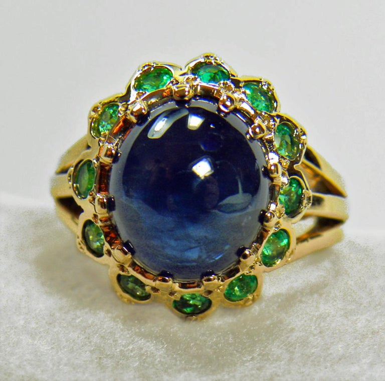 This dazzling 18K yellow gold sapphire emerald ring is centered with a cabochon cut blue Burmese Sapphire, that weighs 7.75 carats. Accenting this beautiful blue sapphire are twelve round green Colombian emeralds weighing 1.25 carat. Total Ring