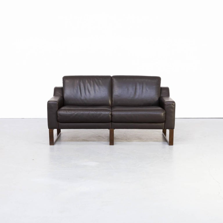 Beautiful brown leather two-seat sofa. The sofa has a wooden frame on which the comfortable leather seating is based. Gives a great spacious look and feel. The set is in good condition consistent with age and use!