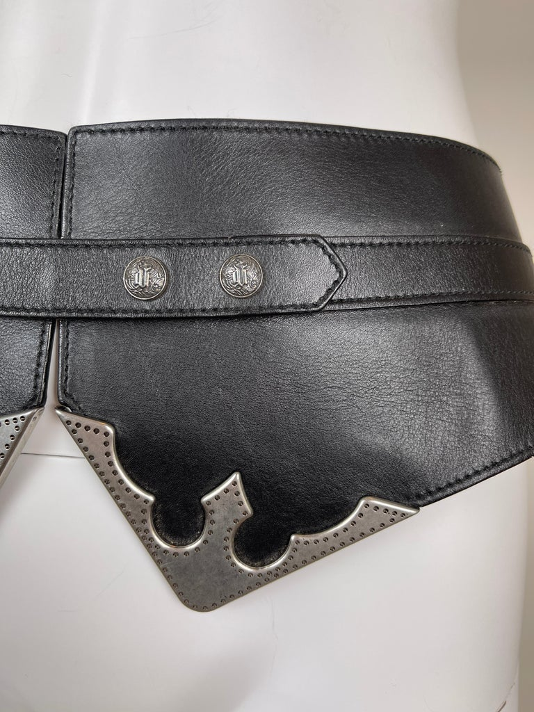 GIANNI VERSACE, Made in Italy, 90's. Black leather corset belt with metallic details and snap buttons.  The size can be adjusted with the snap buttons on the stripe.  Labelled 85cm / 34inch size. Closes at the smallest, the total length is 94cm