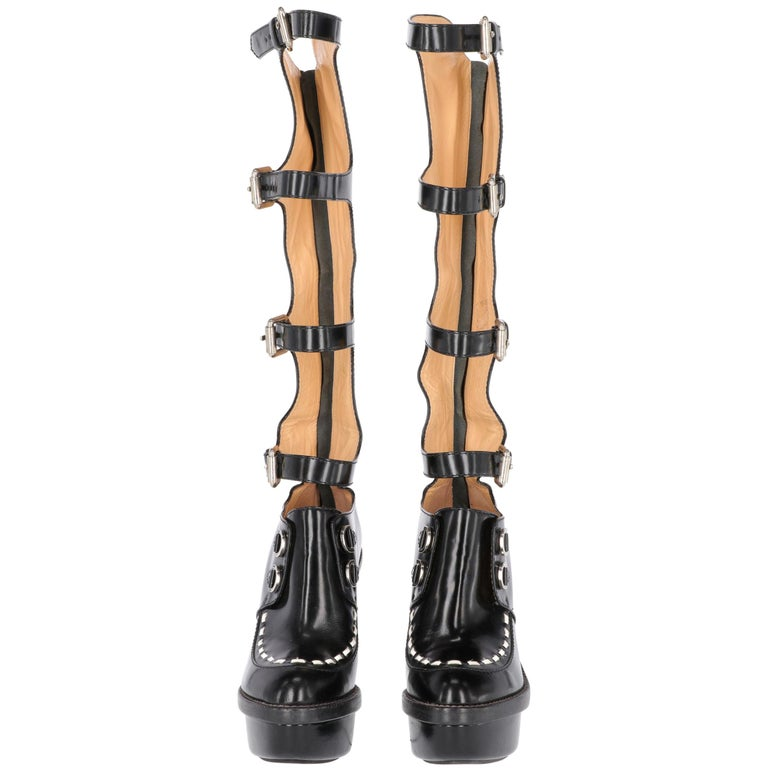Moschino Cheap and Chic Creepers boots, in black leather, with white fake leather insert on the upper, under knee length, back zip fastening and four adjustable buckles on the leg, wide heel 13 cm high covered by small mirrors, leather covered