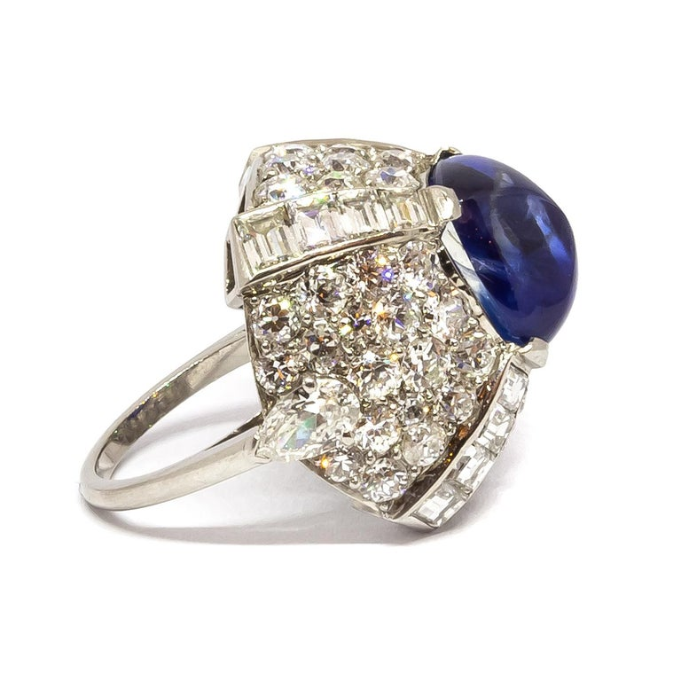 A sapphire and diamond bombé ring, set with a sugar-loaf sapphire weighing 9.10ct in the centre, with pave set round brilliant-cut diamonds and channel set baguette-cut diamonds in the surround, mounted in platinum.