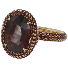 9.13 Carat Oval Cut Garnet with Small Round Cut Garnets in 18 Karat Gold Ring