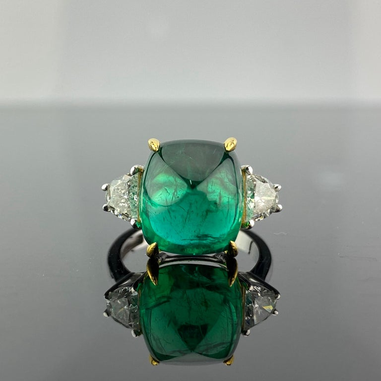 A one-of-a-kind three stone engagement ring, with a 9.15 carat transparent natural Zambian Emerald centre stone and 2 half-moon side stone diamonds. The emerald is of great lustre and has an ideal colour. All set in 18K white gold. Currently a ring