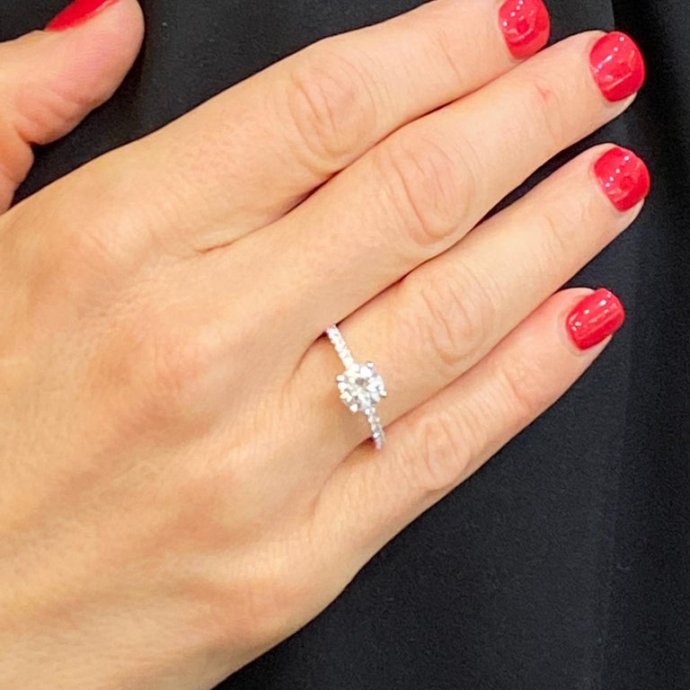 Diamond solitaire engagement ring fashioned in 18 karat white gold. The round brilliant cut diamond weighs .92 carats and is graded I color and VS1 clarity by the GIA. The mounting features round brilliant cut diamonds weighing .40 carat total.