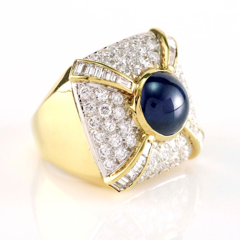 Sapphire and diamond square cocktail ring crafted in 14 karat yellow gold. Size 7. The ring is bead set with 60 full cut diamonds, channel set with 24 baguette cut diamonds, and bezel set with one cabochon cut natural blue sapphire. Total carat