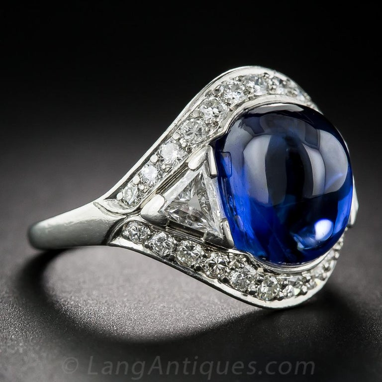 We are pleased to offer one of the finest, most gorgeous and distinctive gemstone rings that's ever come across our counter. An absolutely gemmy, luscious, royal blue cabochon sapphire, weighing 9.60 carats (estimated), radiates and glows from