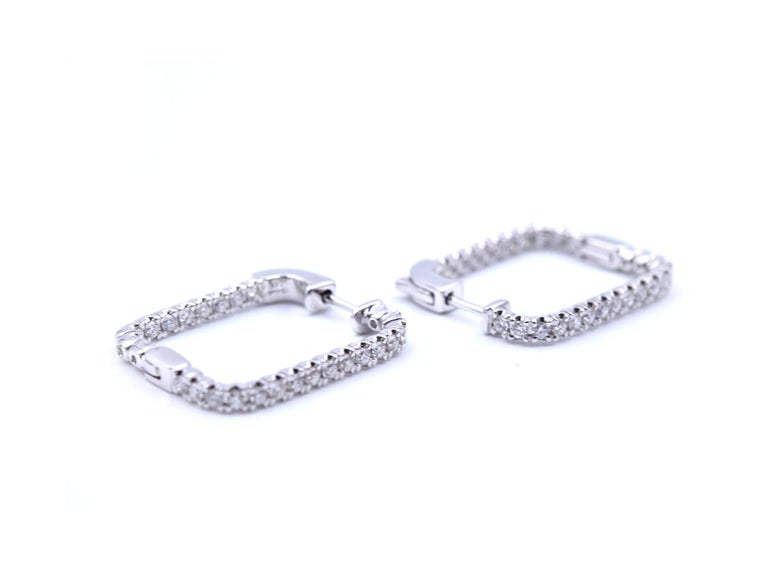 Designer: custom design Material: 14k white gold Diamonds: 52=.97cttw Color: G Clarity: VS Dimensions: 23.27mm drop by 19.35mm width Fastenings: hoop post Weight: 6.19 grams