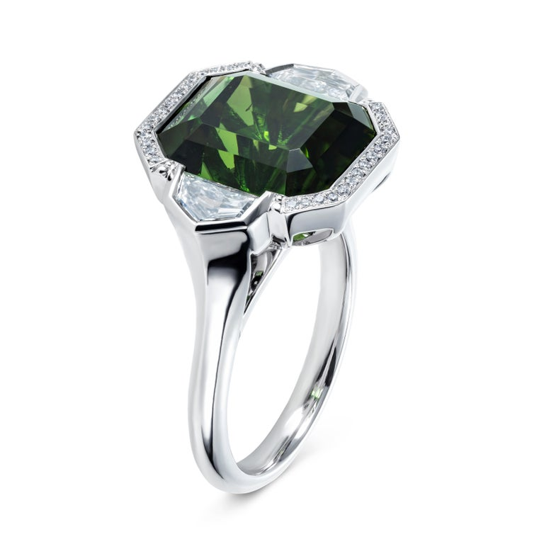 A simply stunning ring featuring a mesmerising green tourmaline.  The design is unique and skilfully made in our London workshop by a team of expert craftsmen.  We spotted the beautiful qualities of this 9.7 carat emerald cut tourmaline in its rough