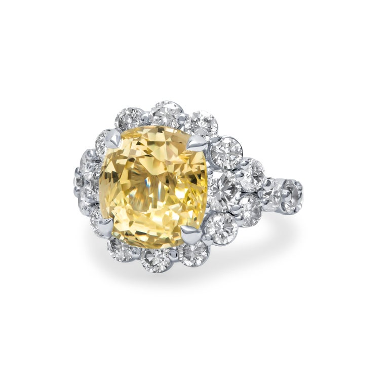 Beautifully hand-crafted 9.79 carat cushion cut natural Ceylon, no heat, yellow sapphire center stone that is set in a custom platinum setting. The stone is accompanied by approximately 3.40 carats total weight of fine round brilliant cut natural