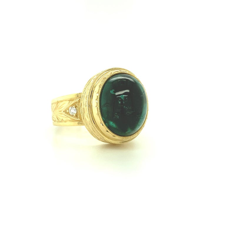 This exquisite, regal-looking dome ring features a fine, 9.80 carat oval green tourmaline cabochon set in a beautifully handmade, hand engraved bezel. The tourmaline has a rich, bluish green body color and has excellent clarity and transparency. The